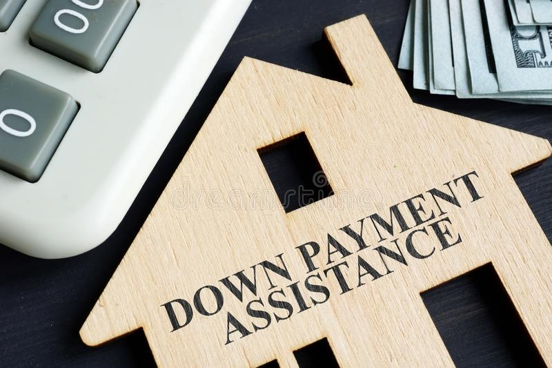 Down payment assistance written on a model of home stock photography