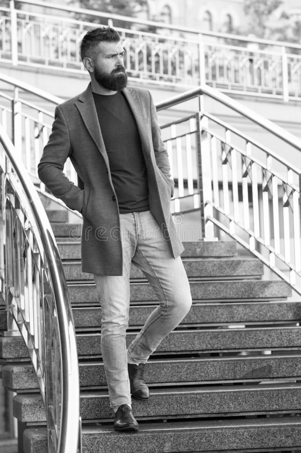 Down the stairs. Stylish casual outfit spring season. Menswear and male fashion concept. Man bearded hipster stylish. Fashionable coat or jacket. Comfortable stock photo