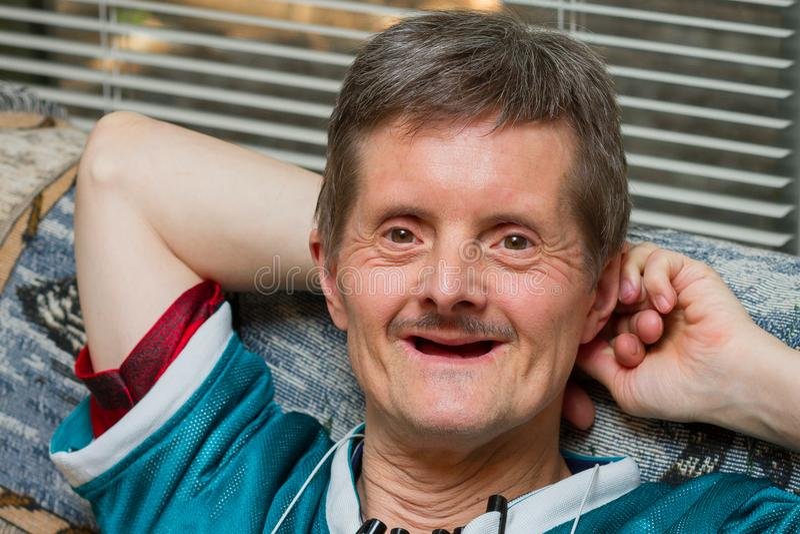 Down-Syndrom Mann keine Zähne, die zurück lächeln lehnen lizenzfreies stockbild