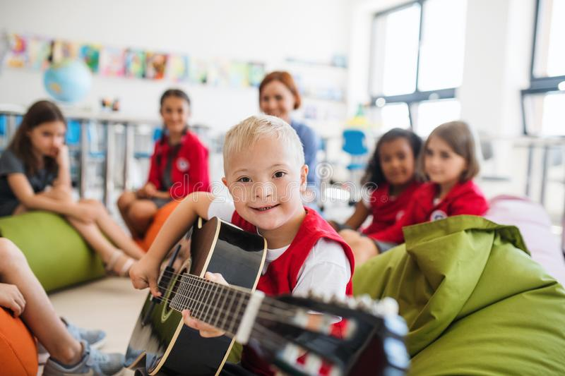 A down-syndrome boy with school kids and teacher sitting in class, playing guitar. A down-syndrome boy with school kids and teacher sitting on the floor in stock images