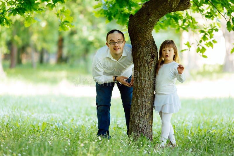 Down Syndrome broder och adoptiv- barn som utomhus spelar royaltyfri foto