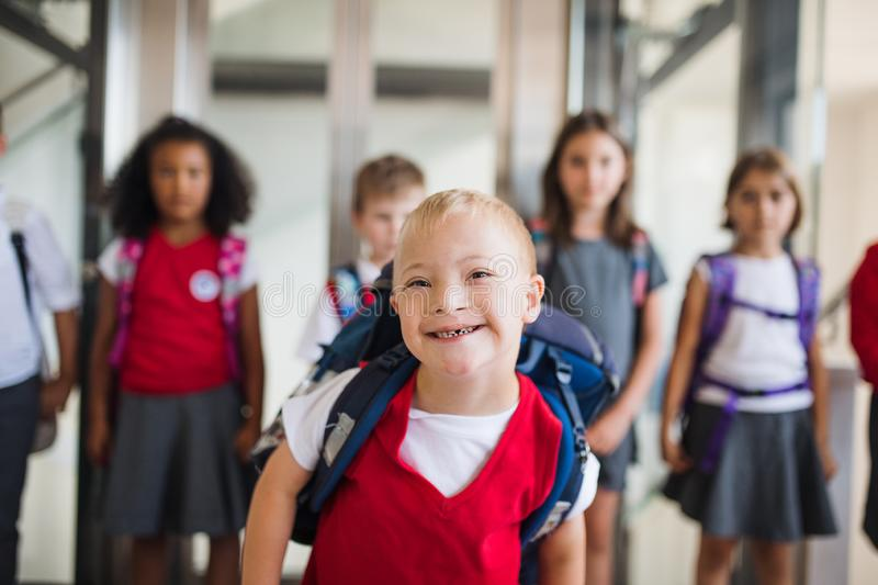 A down-syndrome school boy with group of children in corridor, walking. A down-syndrome school boy with bag and group of children in corridor, walking stock photography