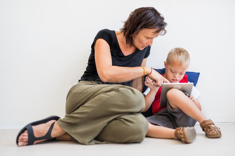 A down-syndrome school boy sitting on the floor with teacher, using tablet. A portrait of down-syndrome school boy sitting on the floor with teacher, using stock photos