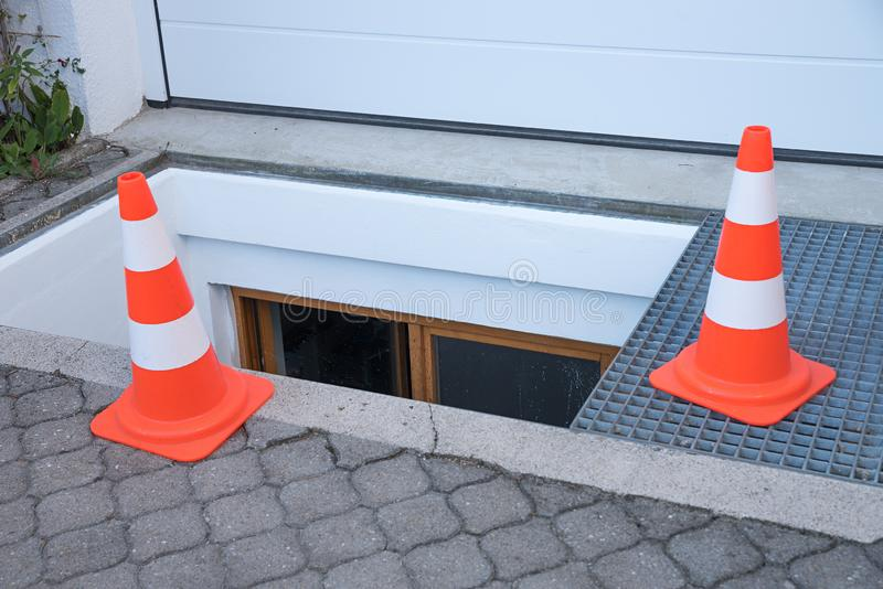 Downfall warning with traffic cones. Open well before the garage, new painted stock photography