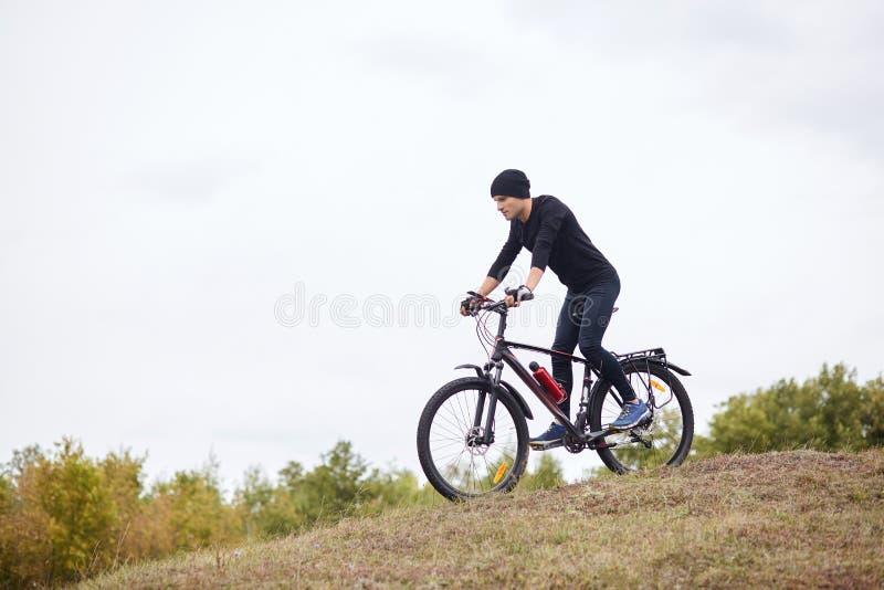 Downhill cycling De mens geniet van het fietsen in de open lucht, met een zwart trainingspak en een kapje, zonder tijd inactief d royalty-vrije stock afbeelding