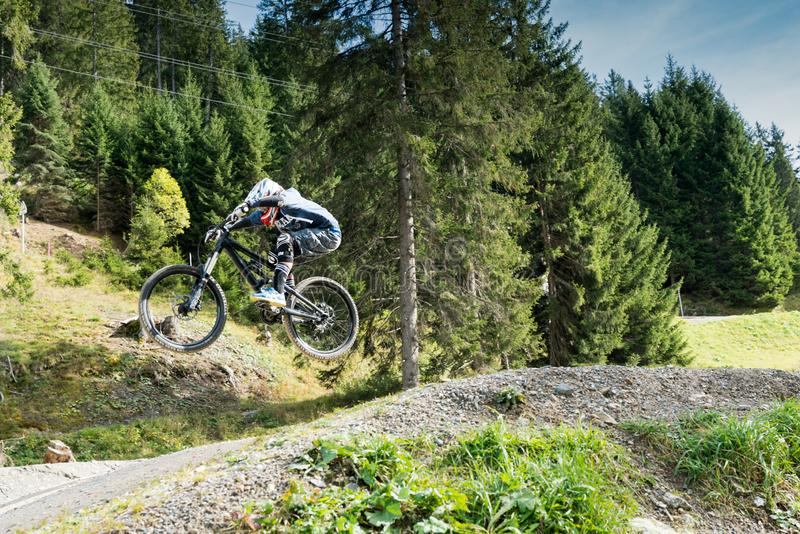 Downhill mountain biker jumping high and riding hard in Lenzerheide in the Swiss Alps royalty free stock photo
