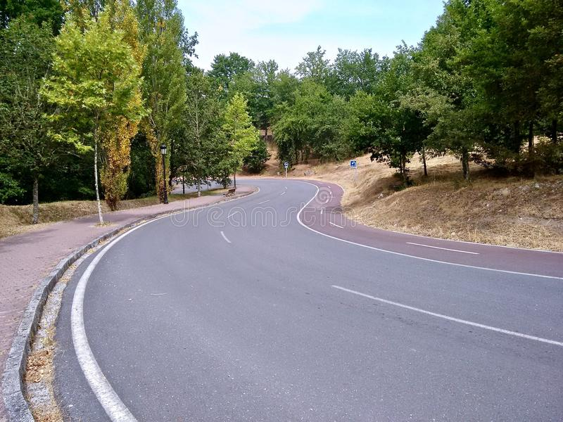 Downhill road in Europe with bike lane to the right. royalty free stock photography