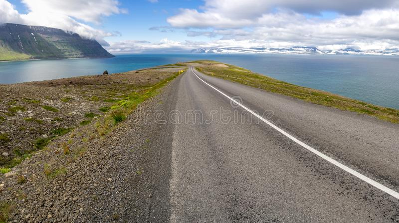 Downhill road near Sudavik in Iceland, Europe. Panorama of downhill road near Sudavik in Iceland, Europe with a hairpin curve and snowy hills in the background royalty free stock photo