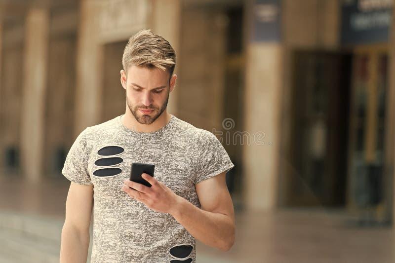 Download application. Man hold smartphone building background. Man messaging online smartphone. Modern smartphone royalty free stock image