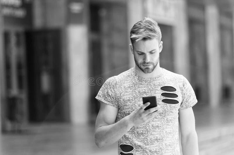 Download application. Man hold smartphone building background. Man messaging online smartphone. Modern smartphone stock image