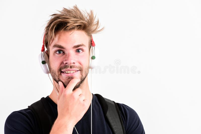 Download music application. Modern people concept. Man tousled hairstyle wear plastic earphones gadget. Enjoy music. Everywhere you go. Youth music taste royalty free stock photos