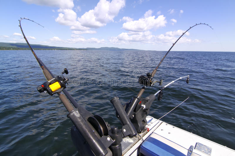 Downrigger fishing rods for salmon, lake trout. A view of downriggers and fishing rods which are used to catch salmon and lake trout on Lake Champlain and around stock photos