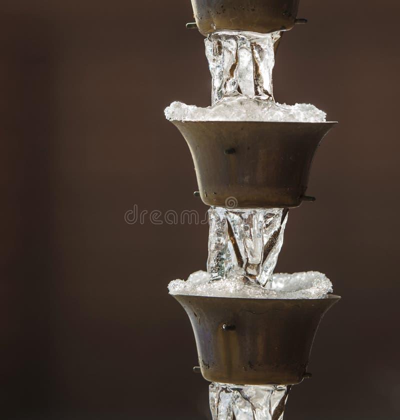 Downspout congelado no fundo de Brown fotos de stock royalty free