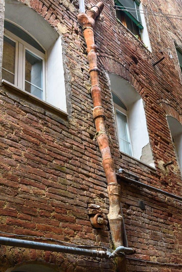 Downspout medieval da argila no degli Orefici de Vicolo da rua em Siena, Toscânia, Itália fotografia de stock royalty free