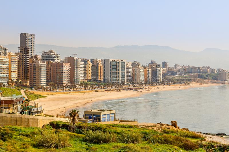 Downtown buildings and towers with road, sandy beach and sea in the foreground, Beirut, Lebanon stock photography
