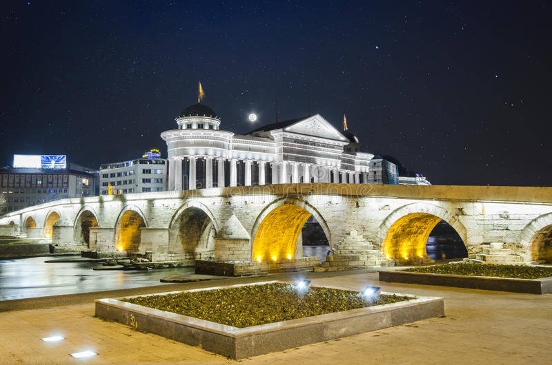 Downtown centre, Skopje, Macedonia. Beautiful old stone bridge and archeological museum of Macedonia on star sky and moon royalty free stock images