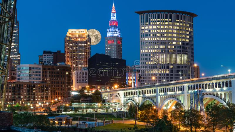 Downtown Cleveland Ohio. Moon Rising Over Downtown Cleveland Ohio Along The Cuyahoga River With City Lights And A Shade Of Evening Blue With Veteran`s Memorial stock images
