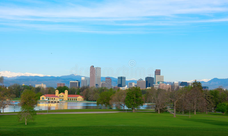 Downtown Denver panoramic skyline buildings with snowcapped mountains and trees. Downtown Denver skyline buildings, on a bright clear summer morning with lake royalty free stock photo