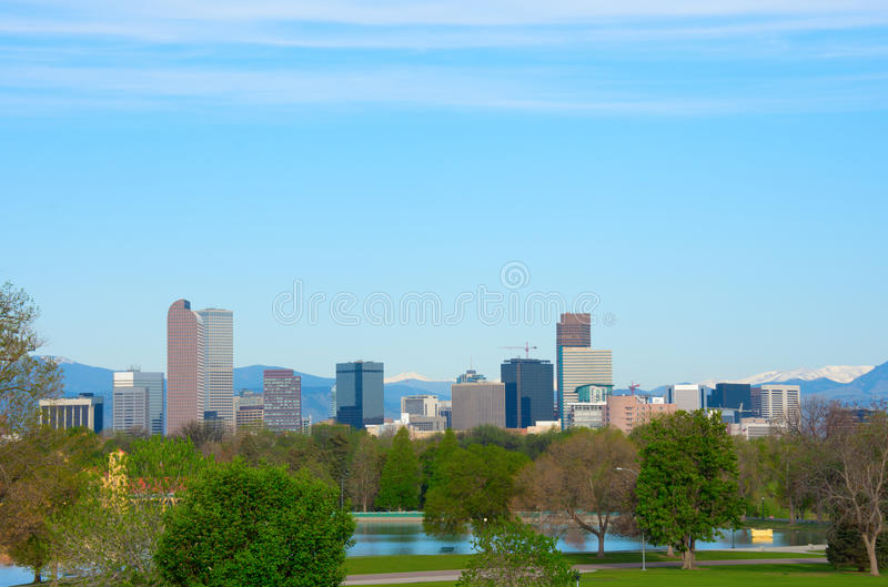 Downtown Denver panoramic skyline buildings with snowcapped mountains and trees. Downtown Denver skyline buildings, on a bright clear summer morning with lake stock images