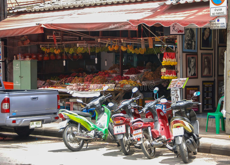 Downtown Phuket. A scene in downtown Phuket, Thailand with fruit vendors and a hair salon. Motorcycles are a popular mode of transportation in this area. Photo royalty free stock images