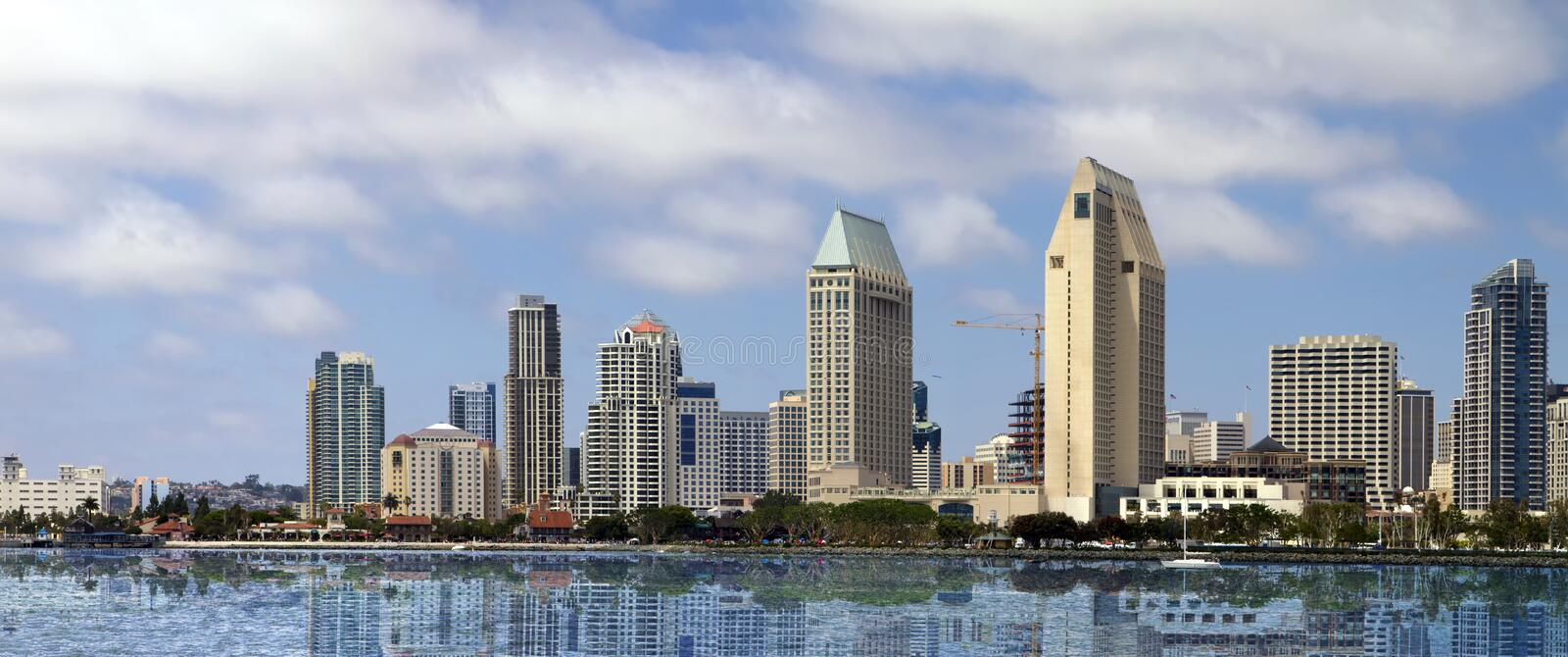 Downtown San Diego Seaside Cityscape. Downtown San Diego waterfront cityscape panorama on a late summer afternoon with reflections of the city in the bay waters stock photo