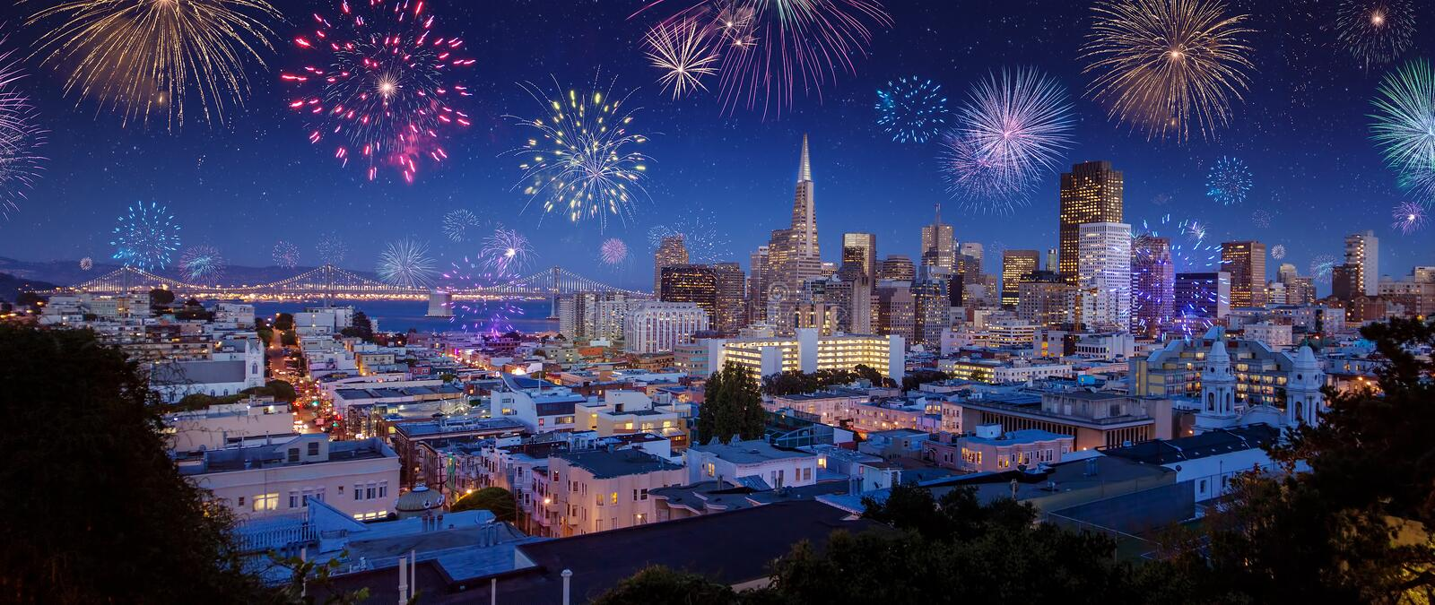 Downtown San Francisco city scape with fireworks on New Years. Downtown San Francisco cityscape with Bay Bridge and flashing fireworks Celebrating New Years Eve stock image