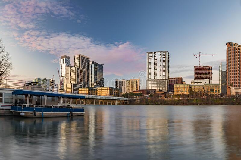 Downtown view across Lady Bird Lake or Town Lake on Colorado River at sunset golden hour in Austin, Texas, USA. Downtown high-rises reflecting sunset golden hour royalty free stock images