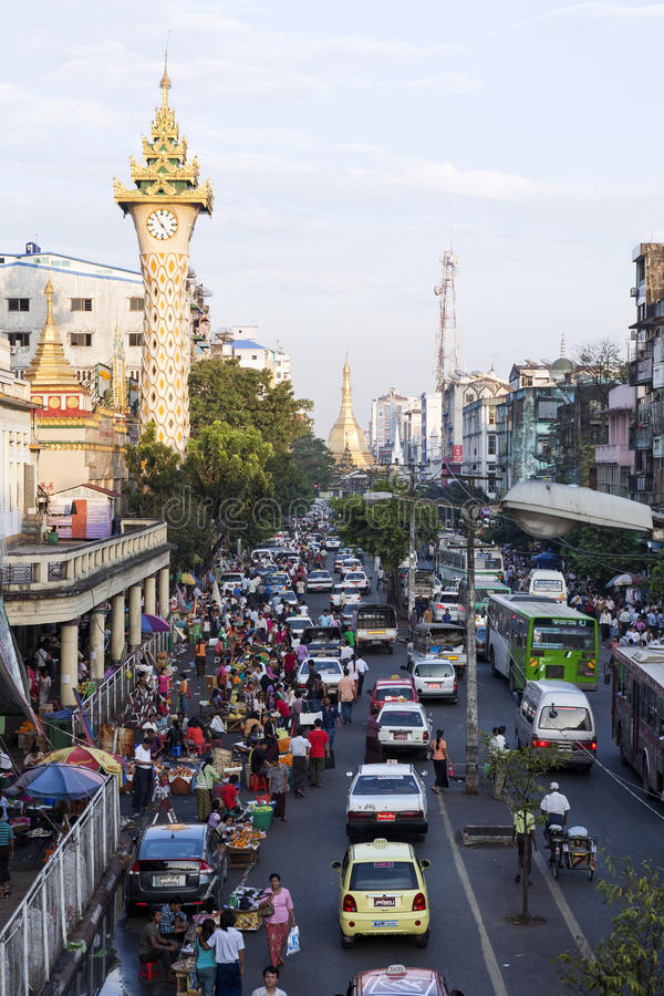 Downtown Yangon. A view of downtown Yangon, looking at Sule Paya in the distance with a Buddhist temple clock tower beside and bustling market activities below royalty free stock photo