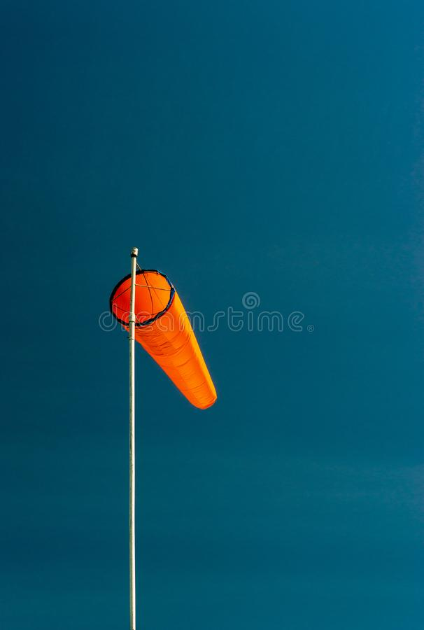 Downward angled plain orange windsock against a clear blue sky. Downward angled plain bright orange windsock on white pole against a clear blue sky stock image