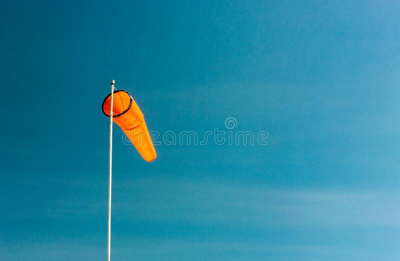 Downward angled plain orange windsock against a clear blue sky. Downward angled plain bright orange windsock on white pole against a clear blue sky stock photos