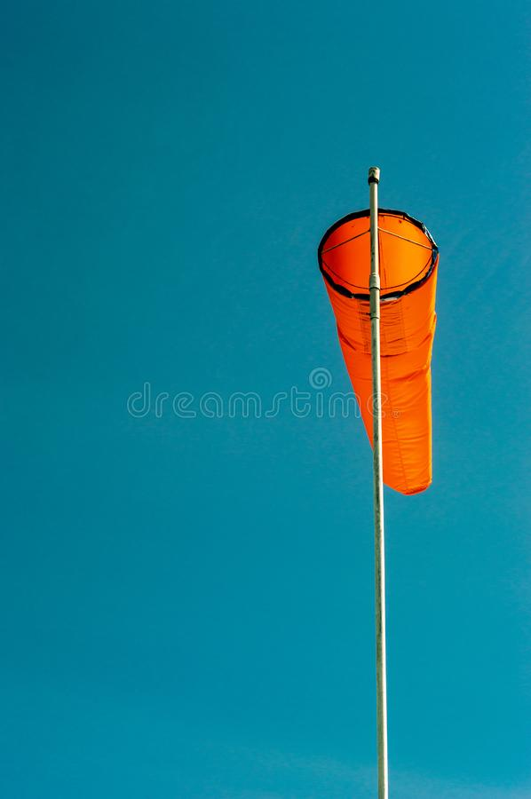 Downward angled plain orange windsock against a clear blue sky. Downward angled plain bright orange windsock on white pole against a clear blue sky royalty free stock images