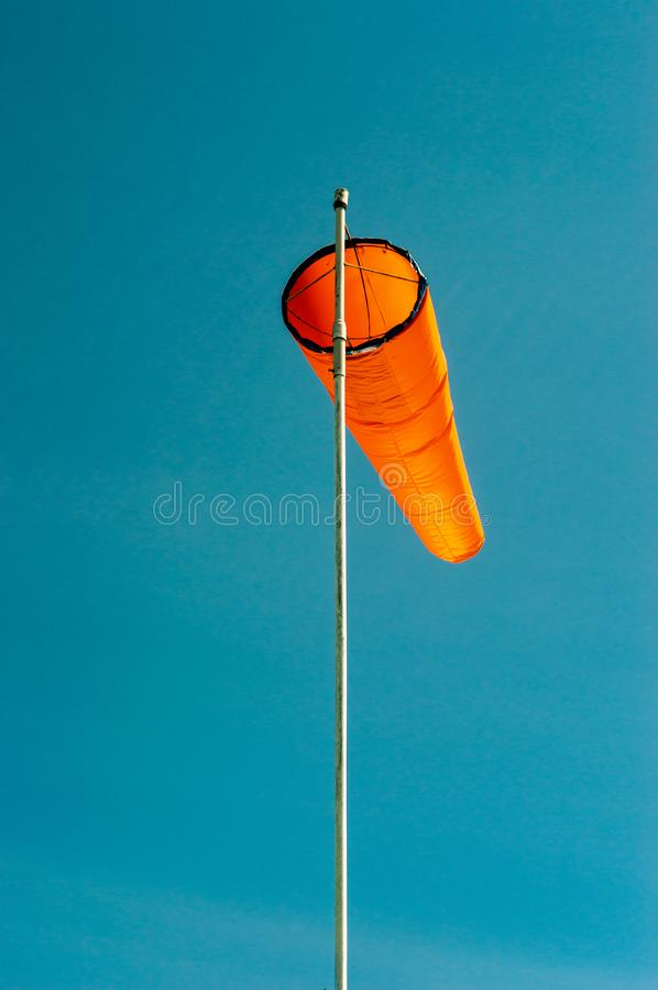 Downward angled plain orange windsock against a clear blue sky. Downward angled plain bright orange windsock on white pole against a clear blue sky stock images
