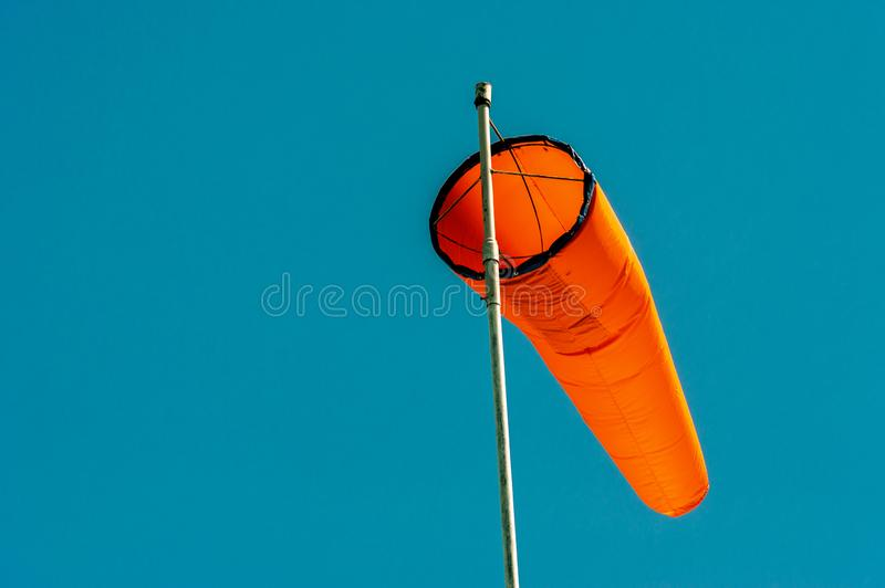 Downward angled plain orange windsock against a clear blue sky. Downward angled plain bright orange windsock on white pole against a clear blue sky royalty free stock photos