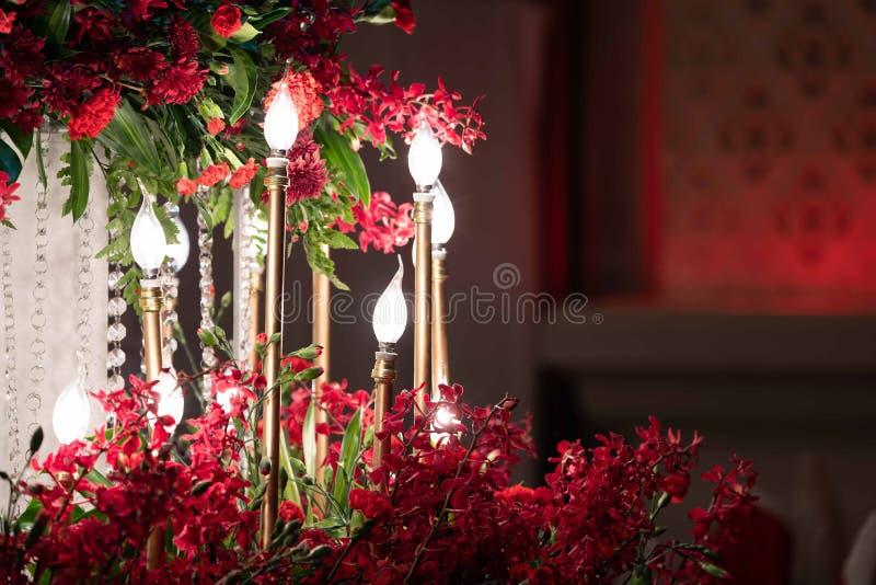 DOWODZONY światło w złocistej świeczce, decored w ślubnym wydarzeniu z czerwoną orchideą wokoło obraz stock