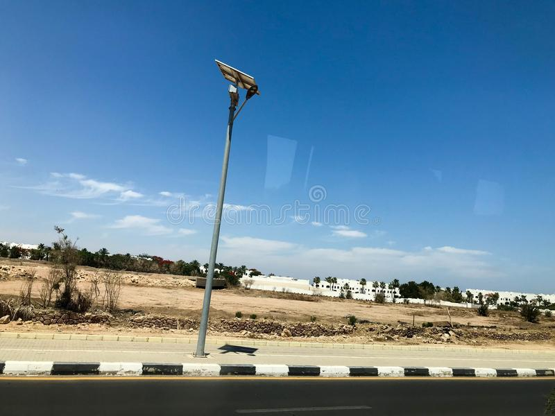 DOWODZONY lamppost z słoneczną baterią na stronie droga w pustyni pod otwartym niebem, tropikalny, południowy, ciepły kurort pod  zdjęcia royalty free