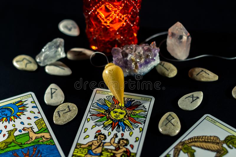 Dowsing Pendulum with Tarot & Runes. A dowsing pendulum with three Tarot cards and various runes stock image