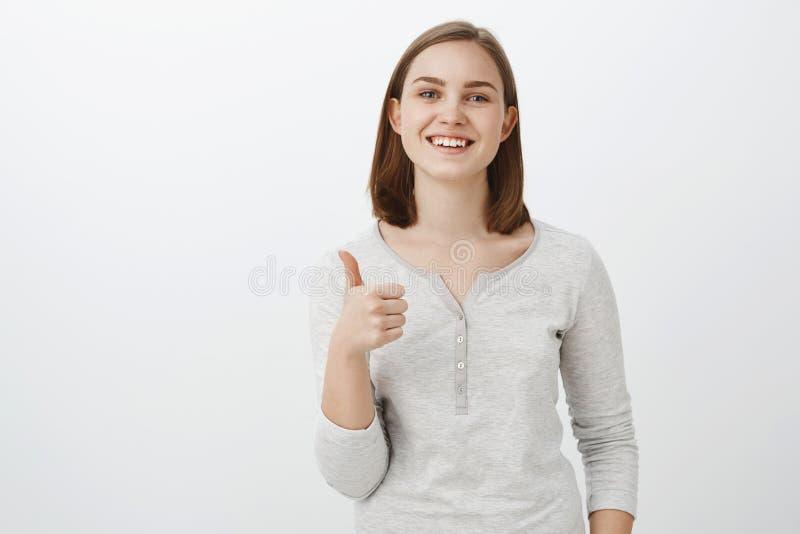 Doy los pulgares de la idea para arriba Mujer europea joven encantadora feliz contenta con el pelo marrón corto que sonríe con al fotografía de archivo libre de regalías