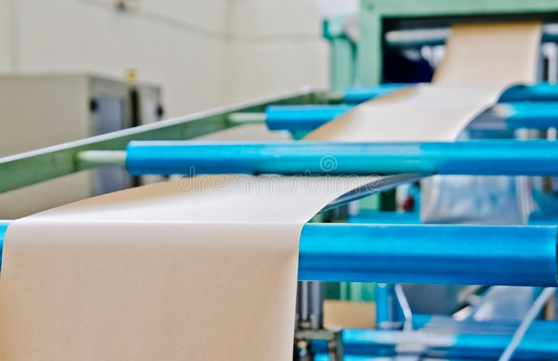 Doypack making packaging machine in modern factory with brown kraft paper rolls and plastic film running stock photo