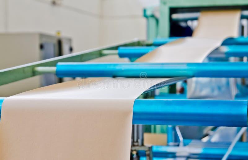 Doypack que hace la empaquetadora en fábrica moderna con los rollos de papel marrones de Kraft y el funcionamiento de la película foto de archivo