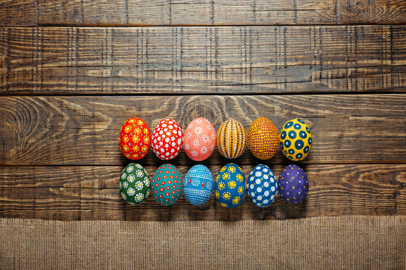 Dozen colorful painted Easter eggs on wooden background. Dozen multicolored Easter eggs painted handmade on a wooden surface royalty free stock images