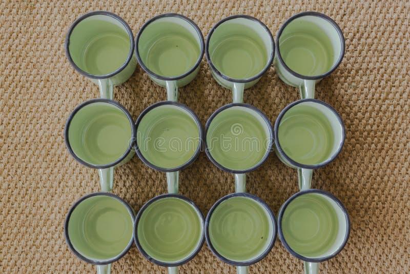 Dozen Cups Tin Metal. Dozen new tin metal green glazed cups together on brown textured carpet royalty free stock photography