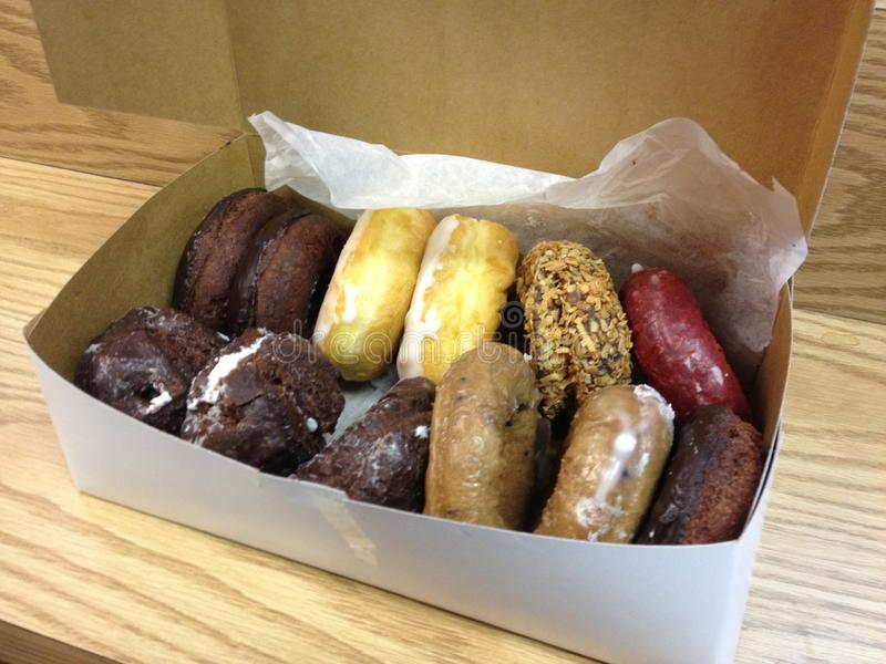 A Dozen Donuts. A box containing a dozen donuts, assorted flavors royalty free stock images