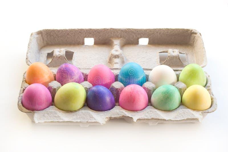 A Dozen Easter Eggs. A Dozen colored Easter eggs in a carton on a white background stock images