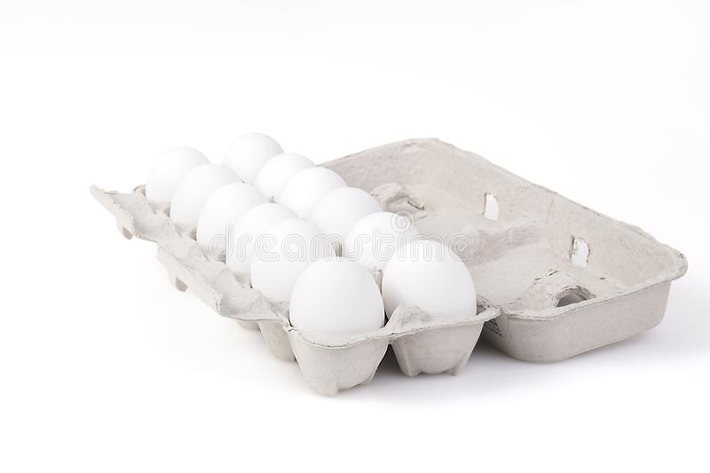 Dozen Eggs In A Carton. A dozen eggs in a carton, isolated on white royalty free stock images