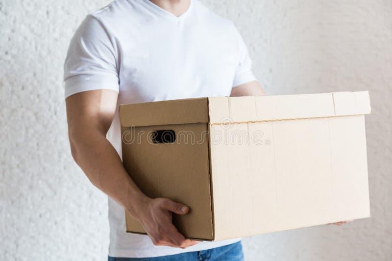 Dozen van het de ladingskarton van de leverings de sterke, spiermens voor zich het bewegen aan een flat professionele arbeider va royalty-vrije stock fotografie