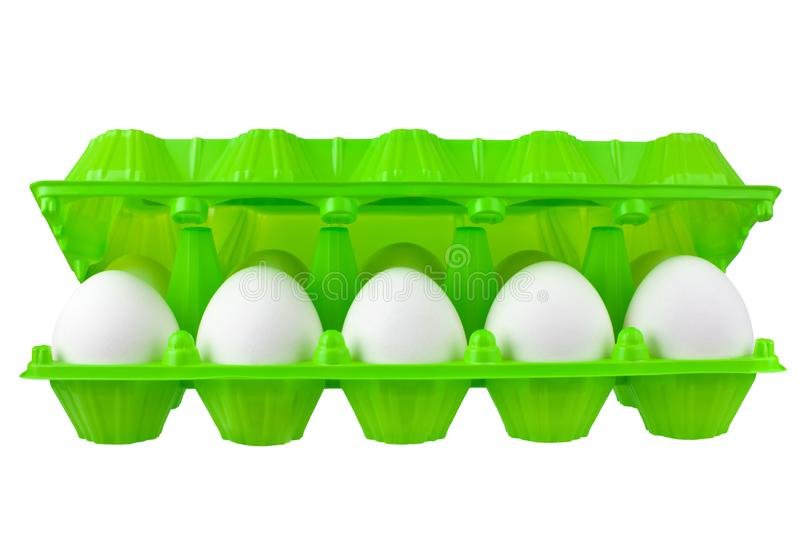 Dozen white eggs in open green plastic package on white background isolated close up front view royalty free stock images