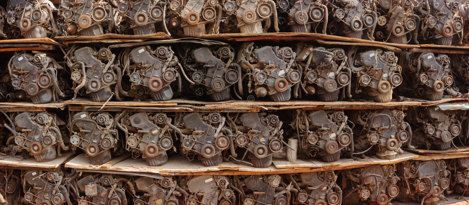 Scrapped Automotive Engines for Sale in a Warehouse. Dozens of salvage car engines, sacked on improvised plywood palets, for sale in an enormous warehouse stock image