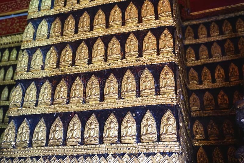 Dozens of tiny golden Buddha medallions line the walls of a temple near Luang Prabang, Laos royalty free stock photos