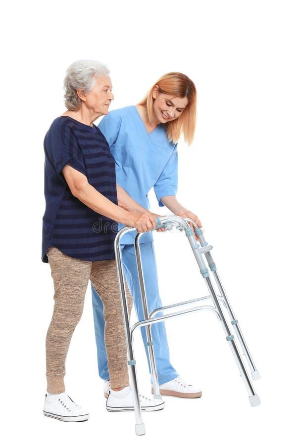 Dozorca pomaga starszej kobiety z odprowadzenie ramą na bielu obraz royalty free