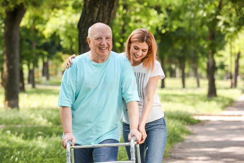 Dozorca starszych osob pomaga mężczyzna z odprowadzenie ramą obrazy royalty free